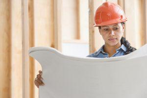 Lanmor Services tech examining technical blueprints